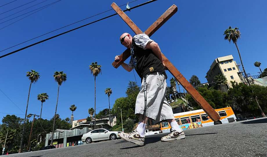 """David Rothschiller carries a cross while walking through the Silver Lake neighbrohood of Los Angeles on Holy Wednesday, April 4, 2012 in California. Rothschiller said he was """" promoting the love of Jesus"""" during Holy Week ahead of Easter Sunday on April 8.  AFP PHOTO/Frederic J. BROWN (Photo credit should read FREDERIC J. BROWN/AFP/Getty Images) Photo: Frederic J. Brown, AFP/Getty Images"""