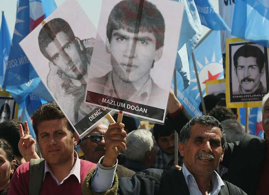 Demonstrators hold portraits of people who they say were executed, died or disappeared in jails during military rule after Turkey's 1980 coup as they demonstrate outside a courthouse in Ankara, Turkey, Wednesday, April 4, 2012.  Thousands of protesters and family members of victims gathered outside the court as an Ankara court began hearing the case against two surviving coup leaders, retired army chief Kenan Evren, 94, and former Air Force commander Tahsin Sahinkaya, 87. The two surviving coup leaders, both in poor health, have been hospitalized and did not attend. Photo: Burhan Ozbilici, Associated Press