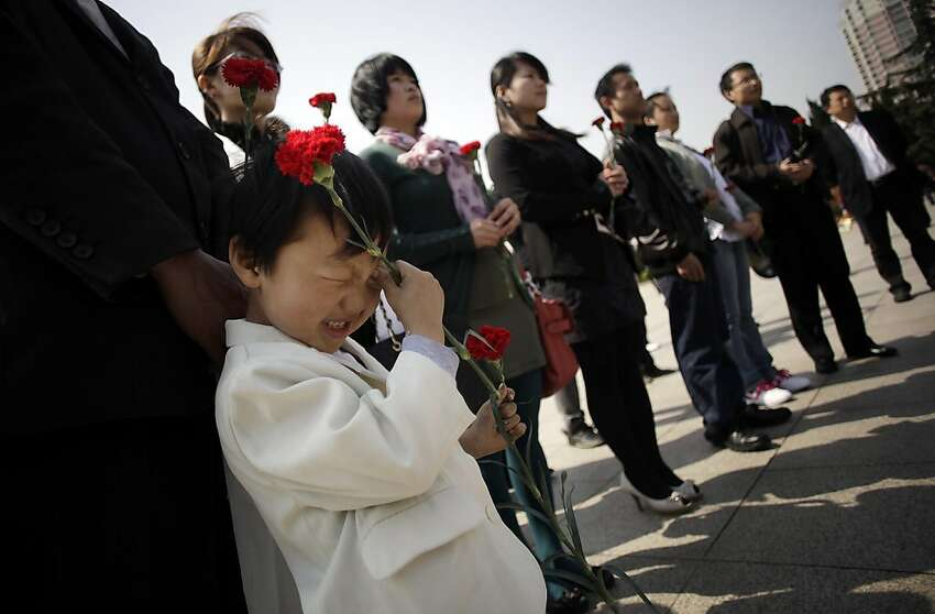People offer a silent prayer for martyrs on Qingming or Grave Sweeping Day at Longhua Martyrs Mausoleum in Shanghai, China Wednesday April. 4, 2012. Qingming is an annual festival where Chinese honor the dead. (AP Photo/Eugene Hoshiko)