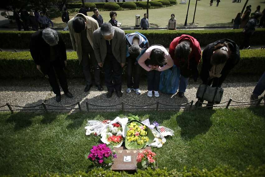 People offer a silent prayer for martyrs on Qingming or Grave Sweeping Day at Longhua Martyrs Mausoleum in Shanghai, China Wednesday, April 4, 2012. Qingming is an annual festival where Chinese honor the dead. (AP Photo/Eugene Hoshiko)
