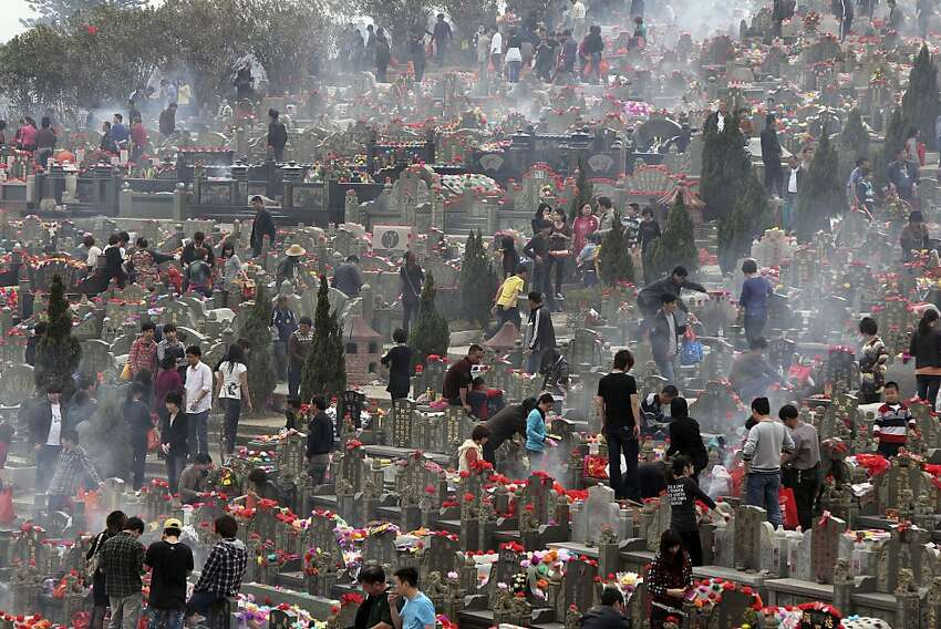 Chinese mourn their deceased family members at a cemetery during Qingming Festival in Jinjiang in southeast China's Fujian province, Wednesday, April, 4, 2012. Qingming festival, also known as Grave Sweeping Day, is a day when Chinese around the world honor the dead by cleaning their tombs and place flowers and offerings at grave sites. (AP Photo) CHINA OUT