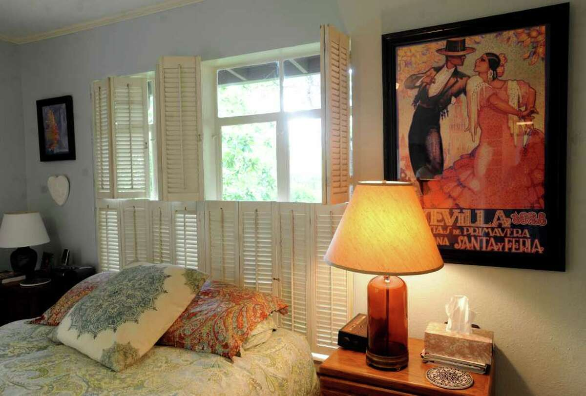 A 1928 poster of the La Feria event in Seville, Spain, adorns a wall in the bedroom of Margaret Mitchell and Doug Endsley. April 3, 2012. Billy Calzada / San Antonio Express-News