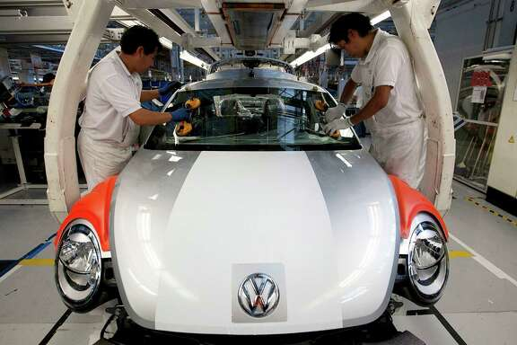 Employees place a windshield on the new generation Volkswagen Beetle at an assembly plant in Puebla, Mexico. Assembly line workers make roughly one-seventh of what U.S. workers make at auto factories.