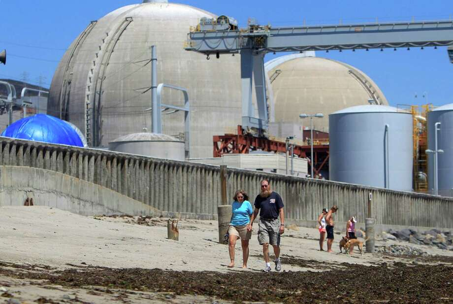 FILE - This file photo taken June 30, 2011 shows beach-goers walking on the sand near the San Onofre nuclear power plant in San Clemente , Calif. The twin reactors at the plant have been idled while investigators determine why tubing carrying radioactive water is eroding at an unusual rate, and the Nuclear Regulatory Commission chairman will visit the plant Friday, April 6, 2012, to highlight the agency's concern over the ailing equipment. (AP Photo, Lenny Ignelzi, File) Photo: Lenny Ignelzi