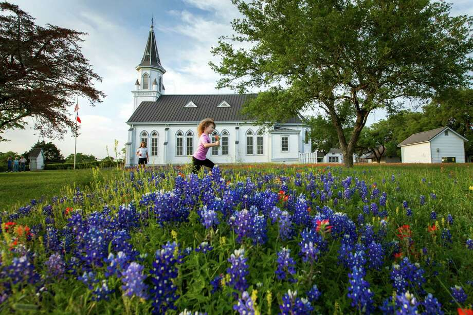DUBINA: Katharina Marie Chaloupka, 4, and Mindy Girard, 9, play among bluebonnets outside Sts. Cyril and Methodius Church after lenten devotions on Thursday, March 29, 2012, in Dubina, Texas. ( Smiley N. Pool / Houston Chronicle ) Photo: Smiley N. Pool / © 2012  Houston Chronicle