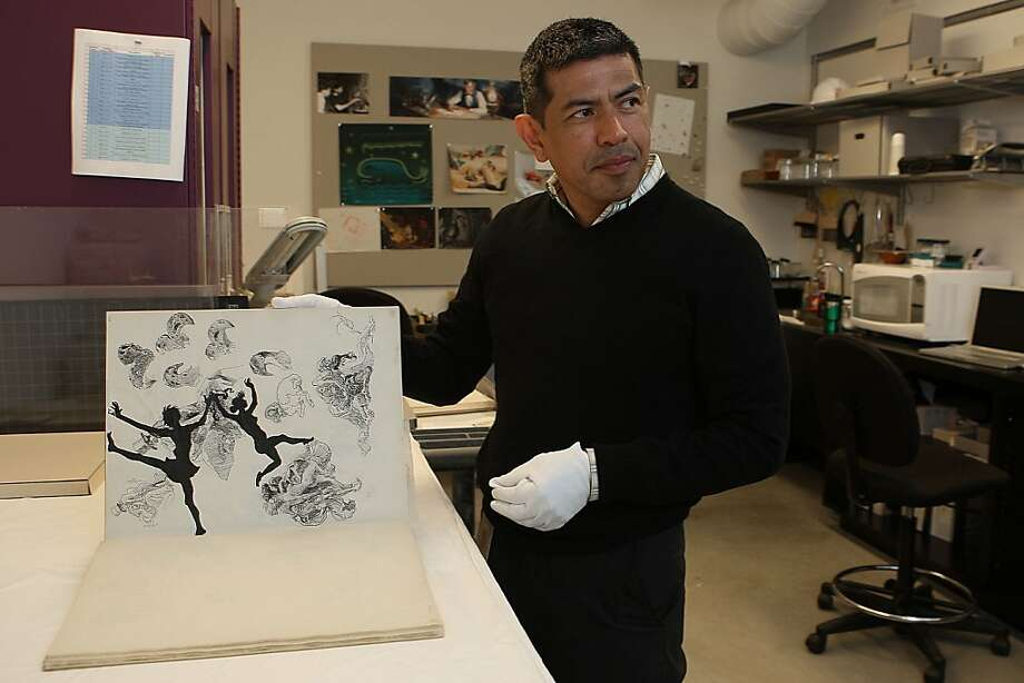 Chief conservator Martin Salazar showing a book of illustrations from the 1930's that Walt Disney would keep for inspiration in the Walt Disney Family Museum in San Francisco, Calif., on Tuesday, February 7, 2012. Photo: Liz Hafalia, The Chronicle