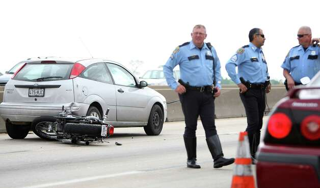 Houston Police officers investigate an accident involving a motorcycle on Highway 290 inbound at the Fairbanks N. Houston Road exit, Thursday, April 5, 2012, in Houston. Photo: Karen Warren, Houston Chronicle / © 2012  Houston Chronicle