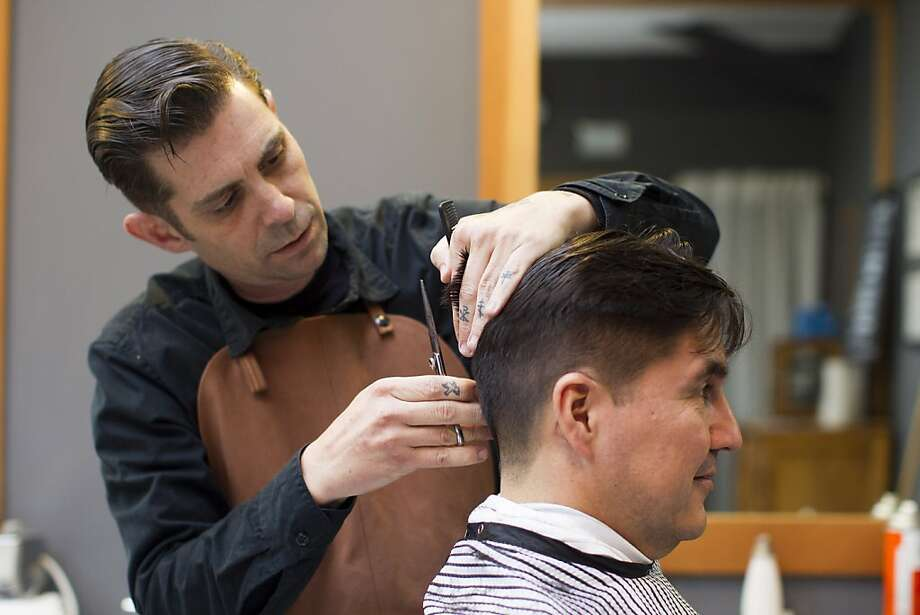 Nicholas Vlahos, co-owner of Temescal Alley Barber Shop, trims hair for customer Carlos Vega, of Oakland, inside his shop in Temescal Alley in Oakland, Calif. on Saturday, March 24, 2012. Photo: Stephen Lam, Special To The Chronicle