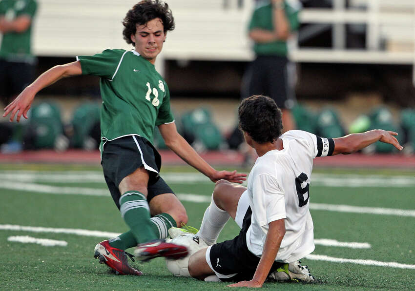 Reagan's Frank Smith comes in to contest with Clark's Vinny Guerrero for possession as the Rattlers play the Cougars in boys soccer playoff action at Comalander Stadium on Thursday, April 5, 2012.