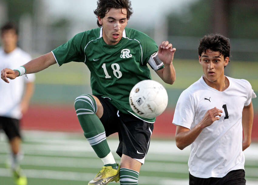 Reagan's Alex Galvan controls against Clark's Manuel Garcia as the Rattlers play the Cougars in boys soccer playoff action at Comalander Stadium on Thursday, April 5, 2012.
