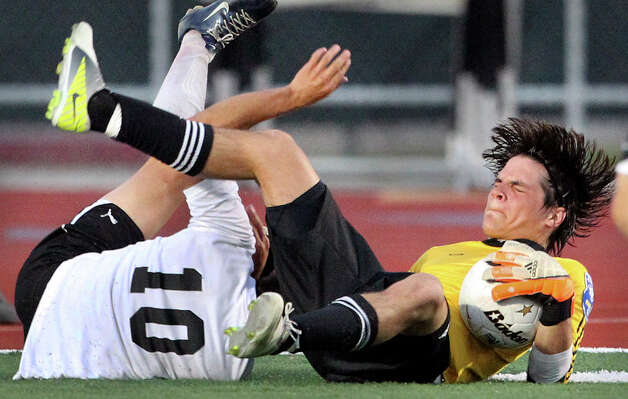 Reagan goalkeeper Andres Hernandez comes down with the ball after battling Clark's Jair Rodriguez at the net as the Rattlers play the Cougars in boys soccer playoff action at Comalander Stadium on Thursday, April 5, 2012. Photo: TOM REEL, San Antonio Express-News / San Antonio Express-News