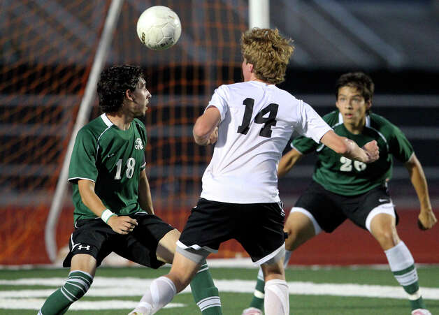 Clark's Joe Klenke tries to punch a shot in past Reagan's Alex Galvan as the Rattlers play the Cougars in boys soccer playoff action at Comalander Stadium on Thursday, April 5, 2012. Photo: TOM REEL, San Antonio Express-News / San Antonio Express-News