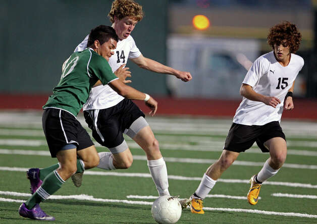 Clark players Joe Klenke (14) and Carlos Sepulveda keep Reagan's Victor Rios closed out as the Rattlers play the Cougars in boys soccer playoff action at Comalander Stadium on Thursday, April 5, 2012. Photo: TOM REEL, San Antonio Express-News / San Antonio Express-News