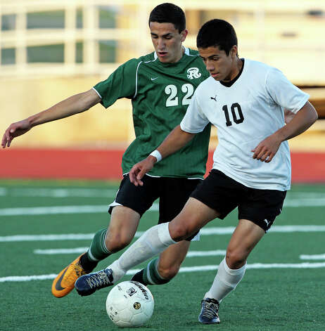 Clark's Jair Rodriguez controls in front of Reagan's Oliver Vilches as the Rattlers play the Cougars in boys soccer playoff action at Comalander Stadium on Thursday, April 5, 2012. Photo: TOM REEL, San Antonio Express-News / San Antonio Express-News