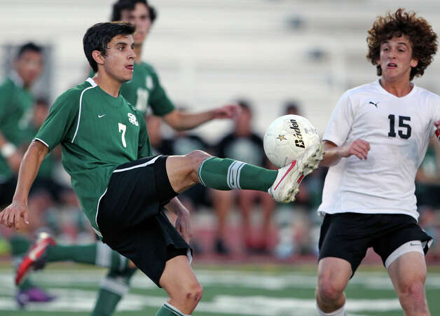 Reagan's Roberto Velazquez cranks into a loose ball as Clark's Carlos Sepulveda moves in as the Rattlers play the Cougars in boys soccer playoff action at Comalander Stadium on Thursday, April 5, 2012. Photo: TOM REEL, San Antonio Express-News / San Antonio Express-News