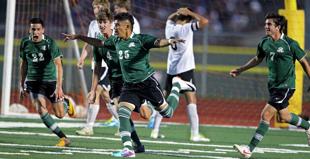 Reagan's Miguel Velasquez celebrates after scoring on a header in the first half as the Rattlers play the Cougars in boys soccer playoff action at Comalander Stadium on Thursday, April 5, 2012. Photo: TOM REEL, San Antonio Express-News / San Antonio Express-News