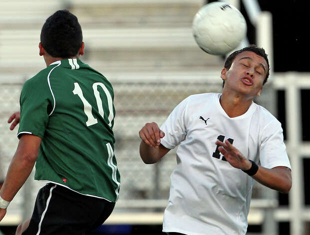 Clark's Ramiro Villalvazo controls a header against Reagan's Victor Rios as the Rattlers play the Cougars in boys soccer playoff action at Comalander Stadium on Thursday, April 5, 2012. Photo: TOM REEL, San Antonio Express-News / San Antonio Express-News