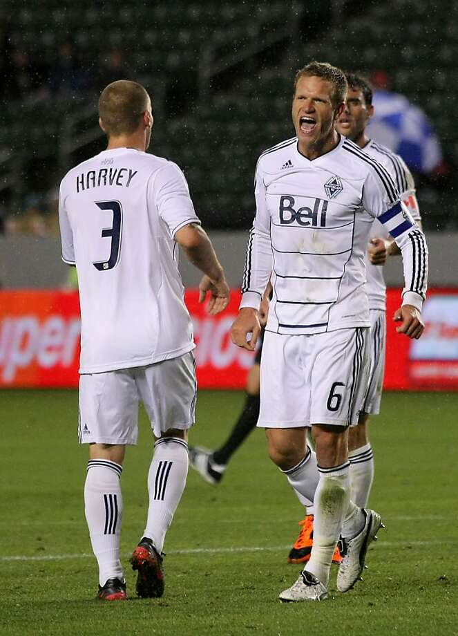 CARSON, CA - MARCH 17:  Jay DeMerit #6 of the Vancouver Whitecaps celebrates with teammate Jordan Harvey #3 after the Whitecaps defeated Chivas USA 1-0 in their MLS match at The Home Depot Center on March 17, 2012 in Carson, California.  (Photo by Victor Decolongon/Getty Images) Photo: Victor Decolongon, Getty Images