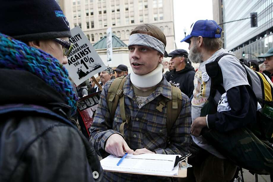 FILE - This Monday, Dec. 12, 2011 file photo shows Iraq war veteran Scott Olsen, who suffered a head injury during a protest in Oakland on Oct. 25, 2011, signing a petition before speaking at a rally at Frank Ogawa Plaza, in Oakland, Calif. Olsen, the Marine Corps veteran whose skull was fractured during an Occupy Oakland protest, was struck by a police beanbag round, not a tear gas canister as initially thought, his lawyer said. (AP Photo/Beck Diefenbach, File) Photo: Beck Diefenbach, Associated Press