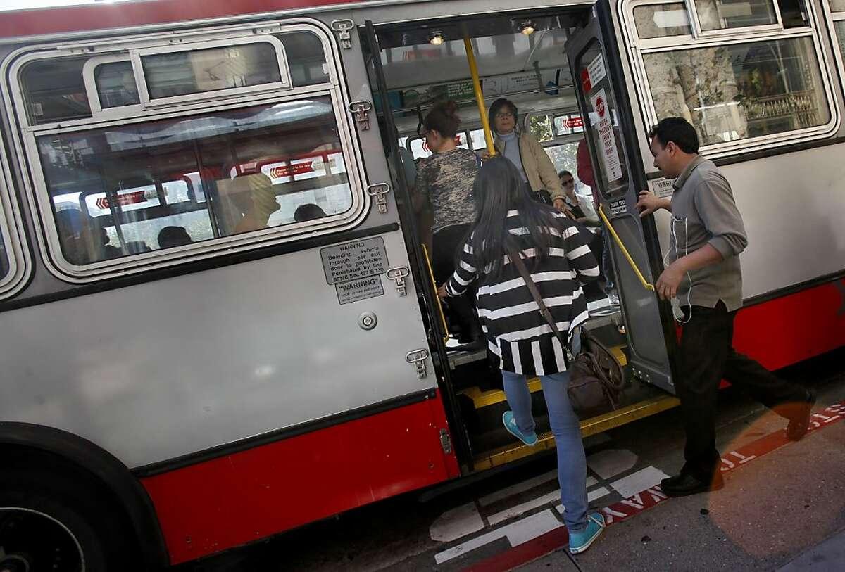 MUNI passengers get on a 49 bus through a rear door as it stops near Geary Blvd.
