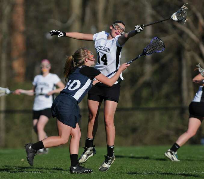 Bethlehem lacrosse player Tori McGrath battles Averill Park's Darian Goyer, left, during Bethlehem's