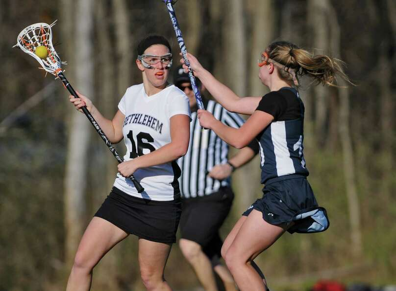 Bethlehem lacrosse player Megan Duffy, left, is defended by Averill Park's Darian Goyer, right, duri