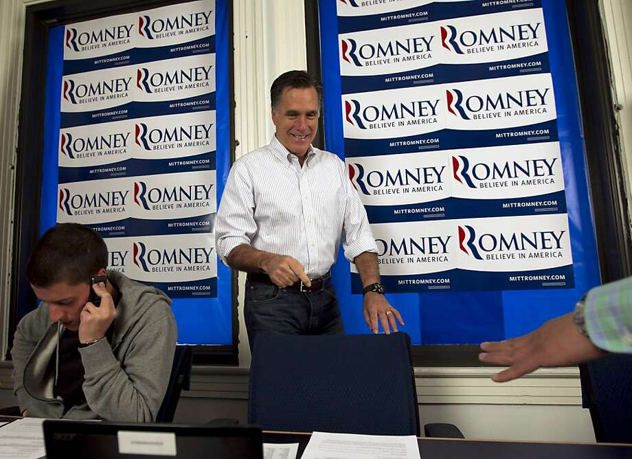 Republican presidential candidate, former Massachusetts Gov. Mitt Romney, center, points to his chair before working the phones at a call center at his Pennsylvania campaign headquarters in Harrisburg, Pa., Thursday, April 5, 2012. Campaign volunteer Jordan Furr of Mechanicsburg, Pa. is at left. Photo: Steven Senne, Associated Press