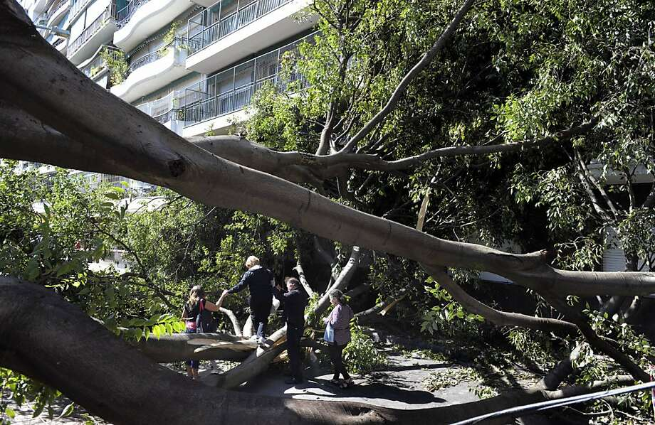 People try to get past a tree that fell during a storm in Buenos Aires, on April 5, 2012. At least 14 people died overnight into Thursday in Argentina following storms that saw strong winds cause damage across the capital region. The Buenos Aires parks and recreation chief said 114 trees had collapsed, destroying many vehicles and blocking roads, while parts of the capital and the suburbs were in the dark after the power was cut. Photo: Juan Mabromata, AFP/Getty Images