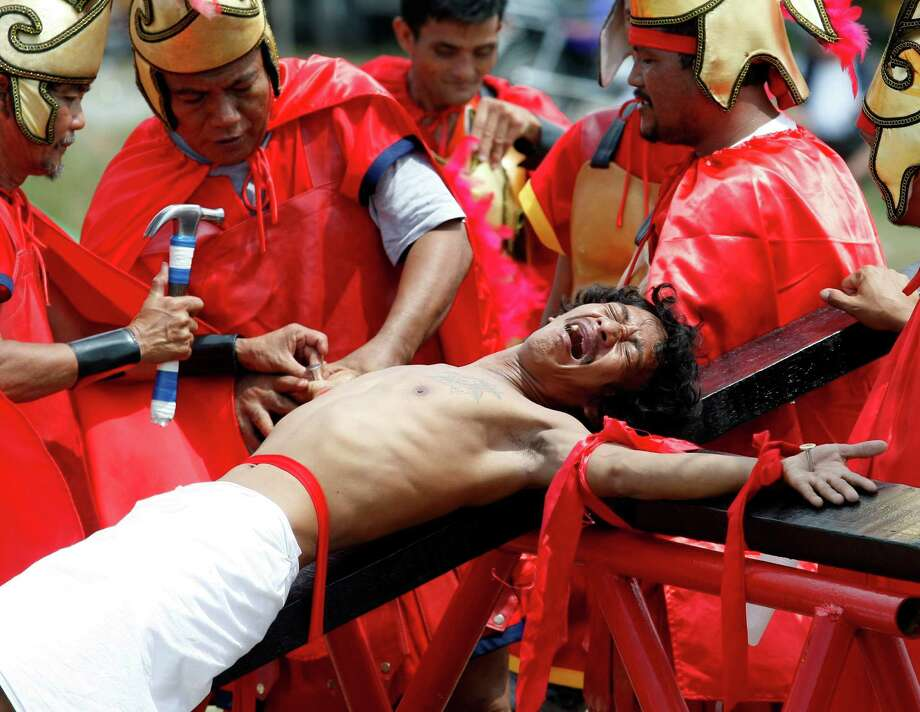 Volunteers dressed as Roman Centurions, drive nails through the palms of an unidentified Catholic devotee in a reenactment of the crucifixion of Jesus Christ on Good Friday at San Pedro Cutud, Pampanga province, north of Manila, Philippines Friday, April 6, 2012. More than two dozen Catholic devotees have themselves nailed on the cross on Good Friday, a practice rejected by the Catholic Church but has become a tourist attraction.(AP Photo/Bullit Marquez) Photo: Bullit Marquez, Associated Press / AP
