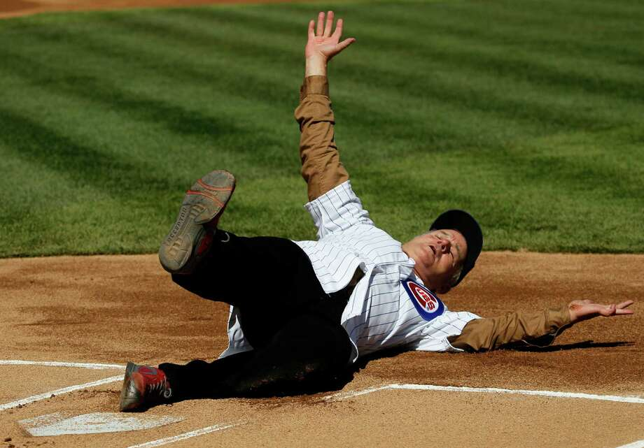 Actor Bill Murray slides into home after rounding the bases before throwing out a ceremonial first pitch before a opening day baseball game between the Chicago Cubs and the Washington Nationals Thursday, April 5, 2012, in Chicago. The Nationals won 2-1. Photo: AP