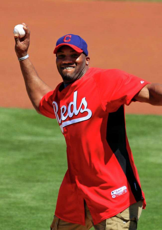 Arizona Cardinals and former Ohio State running back Beanie Wells throws out a ceremonial first pitch before a spring training baseball game between the Cleveland Indians and the Cincinnati Reds, Friday, March 30, 2012, in Goodyear, Ariz. Photo: AP