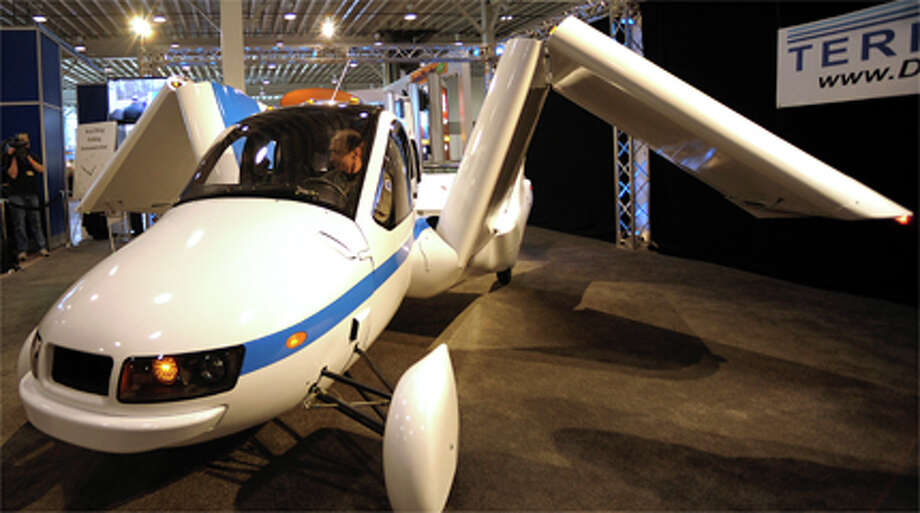 "The Terrafugia Transition ""flying car"" sits on display at the New York International Auto Show in New York, U.S., on Thursday, April 5, 2012. The Terrafugia Transition, developed by a group of Massachusetts Institute of Technology-trained engineers, seats two and can take off and land from more than 5,000 public U.S. airfields. It can be driven on any road and runs on the same gasoline as high-performance cars. Photographer: Peter Foley/Bloomberg Photo: ."