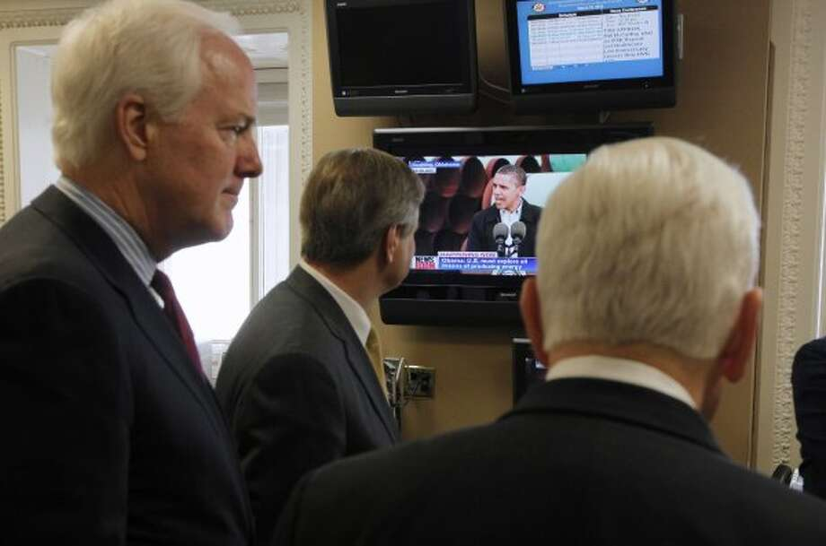 Sen. John Cornyn, Sen. John Hoeven, R-N.D., and Sen. Richard Lugar, R-Ind. watch a monitor as President Barack Obama speaks about the Keystone XL pipeline live from Cushing, Okla., before their news conference on the same subject, Thursday, March 22, 2012, on Capitol Hill in Washington. (Charles Dharapak / The Associated Press)