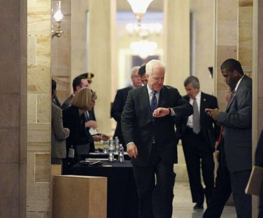 Sen. John Cornyn checks his watch before an unusual closed session in the Old Senate Chamber on Capitol Hill in Washington Monday, Dec. 20, 2010. (Alex Brandon / The Associated Press)