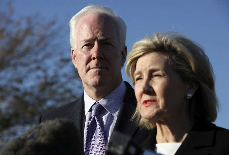 John Cornyn listens to Kay Bailey Hutchison speak during a press conference outside III Corps headquarters Friday Nov. 6, 2009 on Fort Hood Army Base in Fort Hood, Tx. (Edward A. Ornelas / San Antonio Express-News)