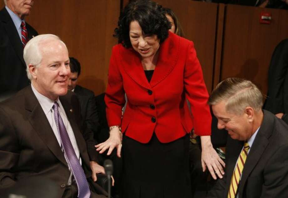 Supreme Court nominee Sonia Sotomayor talks with Sen. John Cornyn and Sen. Lindsey Graham, R-S.C. on Capitol Hill in Washington, Tuesday July 14, 2009, during a break in her confirmation hearing. (Charles Dharapak / The Associated Press)