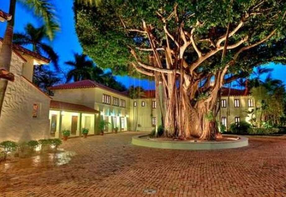 The front exterior of the property features a large motor court that wraps around an enormous tree. Photo: EWM.com