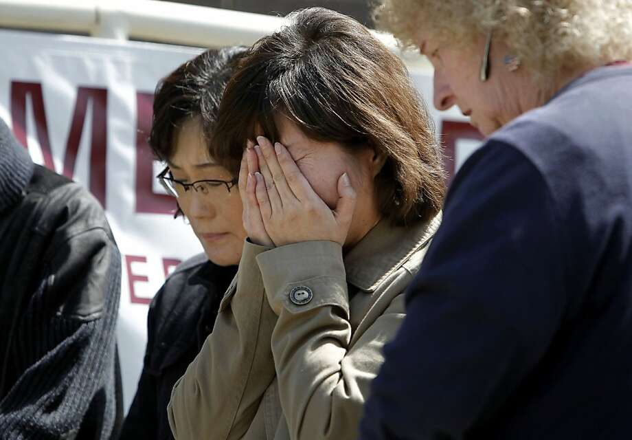 School administrator, Hwang Sun Seon, (cenetr) is comforted by fellow workers as students and faculty hold a memorial in front of Oikos University in Oakland, Ca. on Friday April 6, 2012, the site of a mass shooting that left seven people dead on Monday April 2. Photo: Michael Macor, The Chronicle