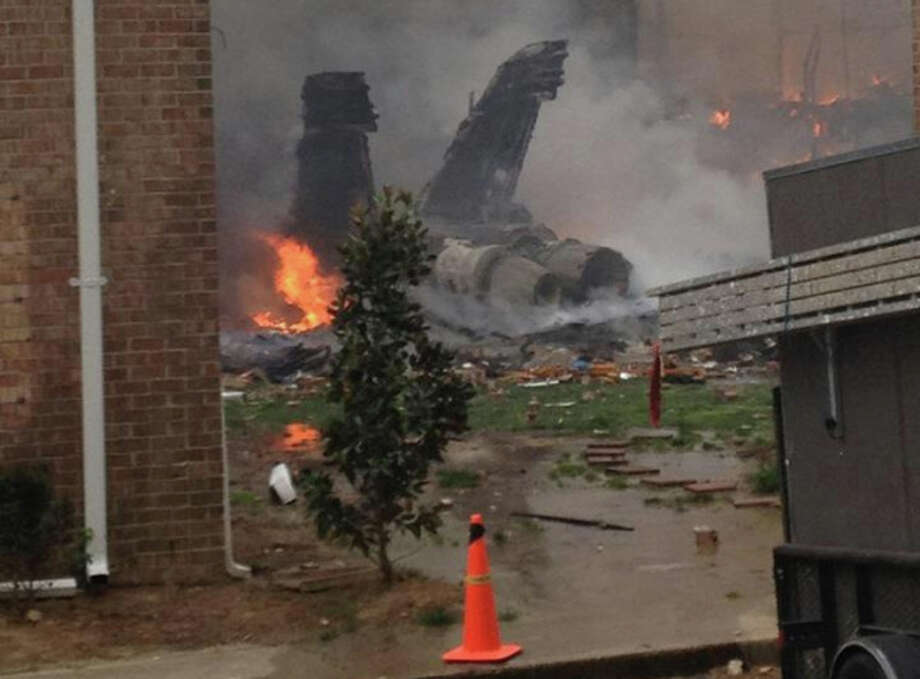 The burning fuselage of an F/A-18 Hornet lies smoldering after crashing into a residential building in Virginia Beach, Va., Friday, April 6, 2012. The Navy did not immediately return telephone messages left by The Associated Press, but media reports indicate the two aviators were able to eject from the jet before it crashed. They were being treated for injuries that were not considered life threatening. (AP Photo) / AP