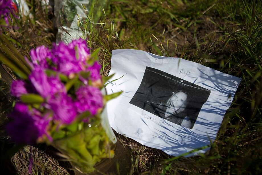 OAKLAND, CA - APRIL 4:  A photo of victim Doris Chibuko rests next to flowers at a memorial in front Oikos University where a gunman had gone on a shooting rampage, April 4, 2012 in Oakland, California. Six students and one employee were killed on Monday when a gunman opened fire at Christian-based Oikos University. The suspect One Goh, a former nursing student at the school, was arrested shortly after the shooting and is expected to make his first court appearance.  (Photo by Jonathan Gibby/Getty Images) Photo: Jonathan Gibby, Getty Images