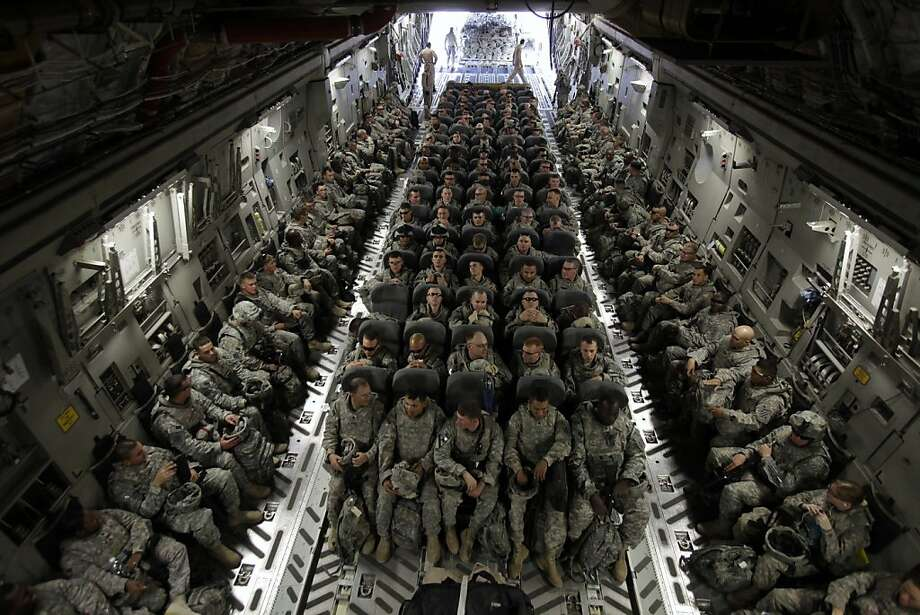 FILE - In this Nov. 30, 2010 file photo, members of 1st Brigade, 3rd Infantry Division, based at Fort Stewart, Ga., sit in the belly of a C-17 aircraft at Sather Air Base in Baghdad as they begin their journey home after a year in Iraq. President Barack Obama on Friday Oct. 21, 2011 declared an end to the Iraq war, one of the longest and most divisive conflicts in U.S. history, announcing that all American troops would be withdrawn from the country by year's end. (AP Photo/Maya Alleruzzo, File) Photo: Maya Alleruzzo, Associated Press