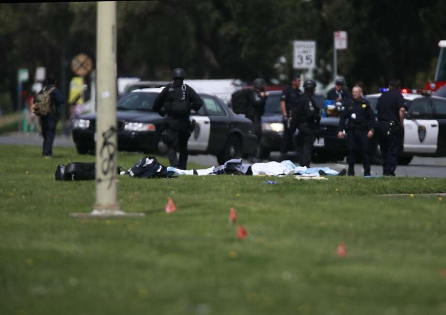 With bodies lying on the grass, Police and others authorities organize outside Oikos University were several people were killed and more are wounded after on Monday April 2, 2012 in Oakland, Calif. Photo: Mike Kepka