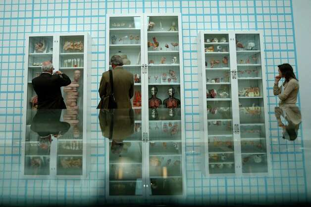 "People are reflected as they look at British artist Damien Hirst's year 2000 piece ""Trinity - Pharmacology, Physiology, Pathology,"" consisting of glass, faced particle board, wood, steel and anatomical models, at the Tate Modern gallery in London. Photo: Matt Dunham, Associated Press / AP"