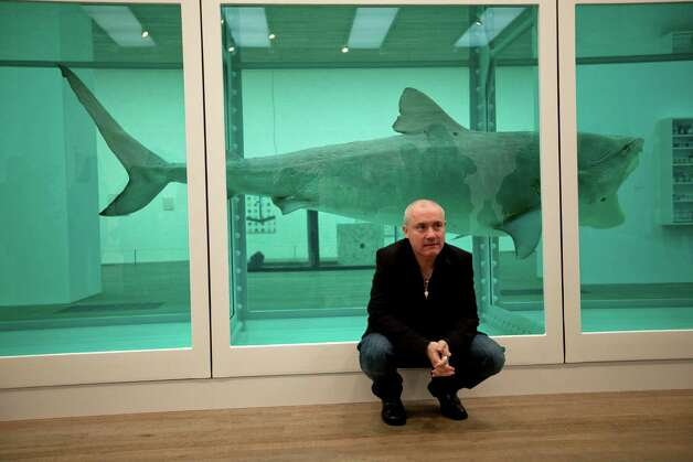"British artist Damien Hirst beside the 1991 piece ""The Physical Impossibility of Death in the Mind of Someone Living,"" a tiger shark preserved in formaldehyde in a vitrine.