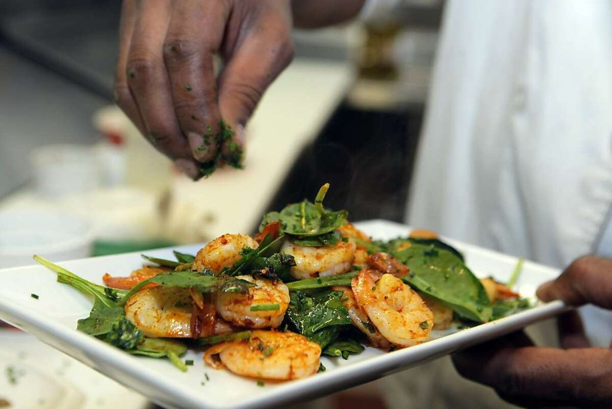 Eskender Aseged, Radio Africa & Kitchen chef, prepares a berbere prawns dish with spinach.