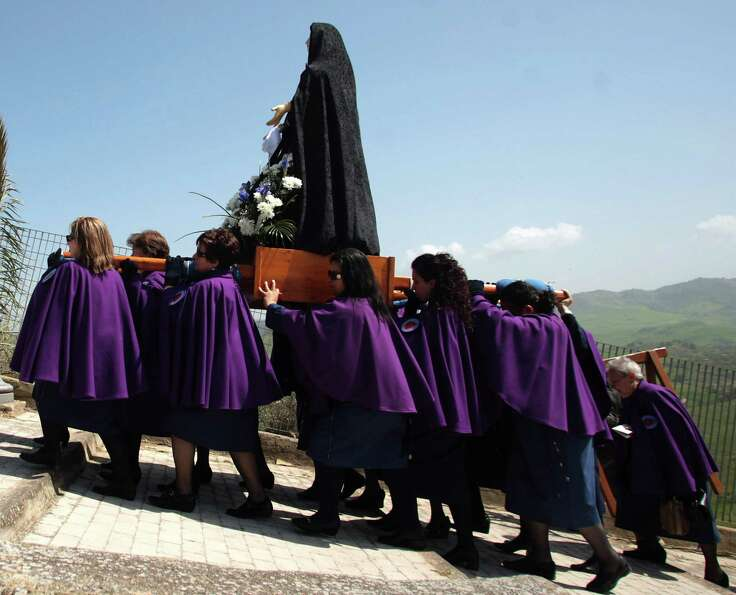 Women carry a statue during the Good Friday procession in Villarosa on the Italian island of Sicily