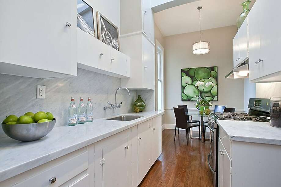 In the eat-in-kitchen, light streams into the bright white space through an overhead skylight. Granite countertops and decorative fixtures are among the other kitchen highlights. Photo: OpenHomesPhotography.com