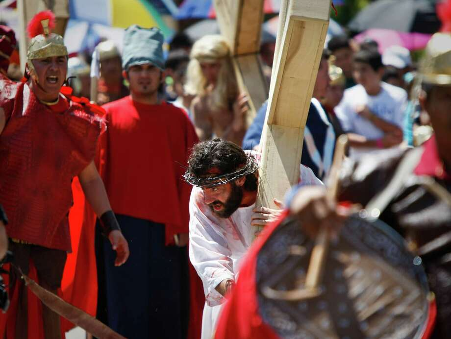 Jesus, portrayed by Father David Bergeron, carries his cross as Roman soldiers and enemies yell at him during a live reenactment of the stations of the cross, Friday, April 6, 2012, at Queen of Peace Church in Houston. Photo: Nick De La Torre, Houston Chronicle / © 2012  Houston Chronicle