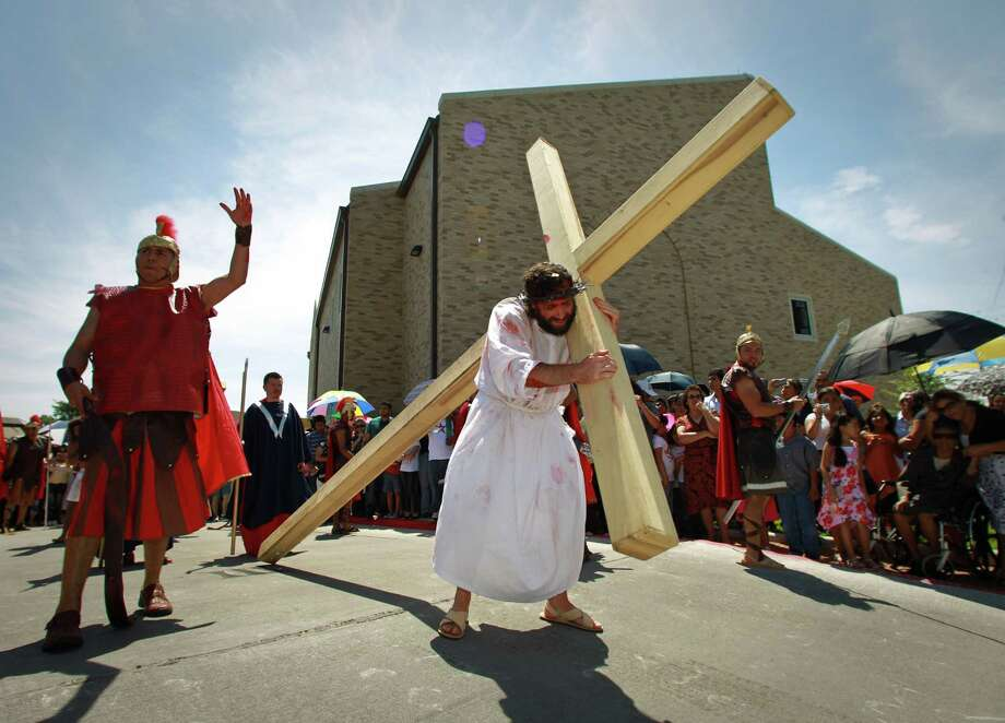 Jesus, portrayed by Father David Bergeron, is forced to carry the cross for his crucifixion on during a live reenactment of the stations of the cross, Friday, April 6, 2012, at Queen of Peace Church in Houston. Photo: Nick De La Torre, Houston Chronicle / © 2012  Houston Chronicle