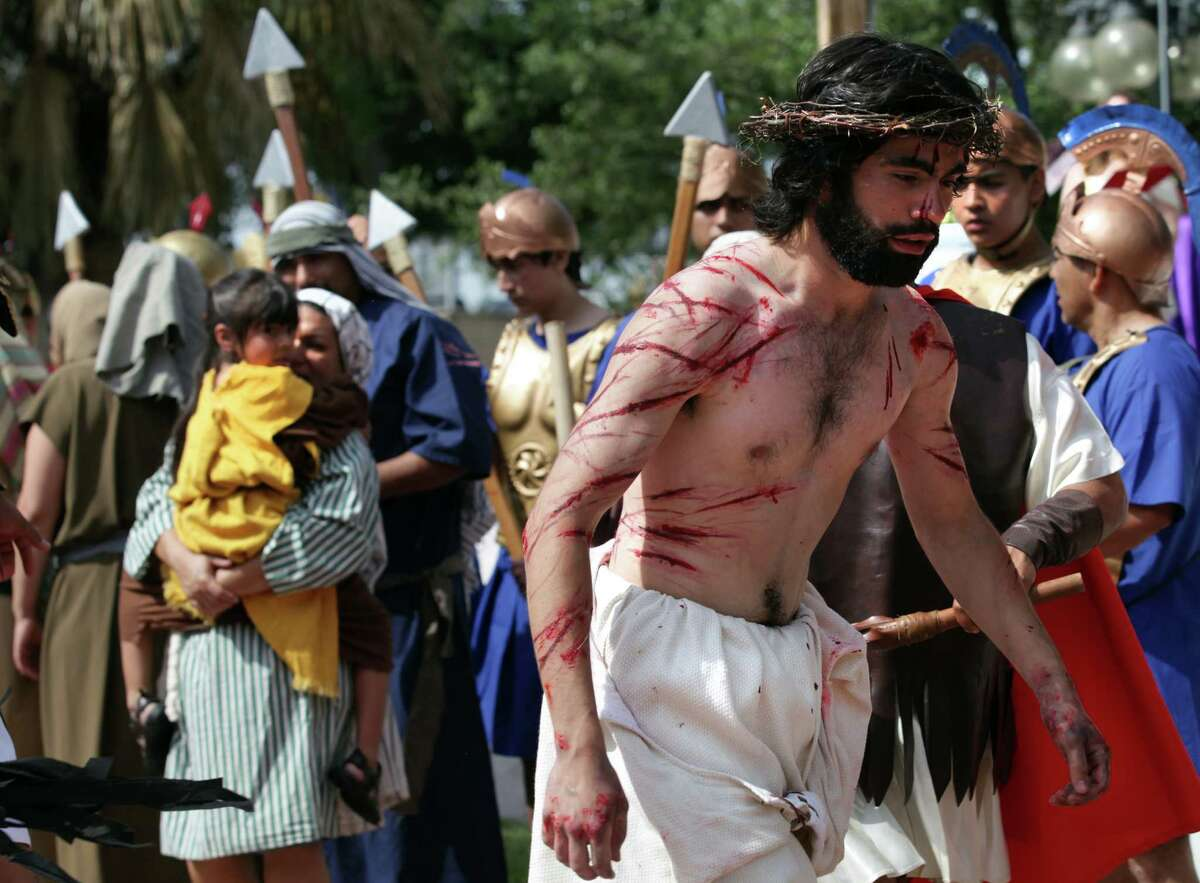 Jesus, played by Mario Jr. Mandujano, is stared at by a mother and her daughter during The Passion Play, a re-enactment of the suffering of Christ leading to his crucifixion in front of San Fernando Cathedral. Friday, April 6, 2012. Bob Owen/San Antonio Express-News.